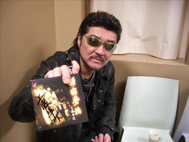 『新宿夢鴉』のジャケットにサインをする小沢仁志