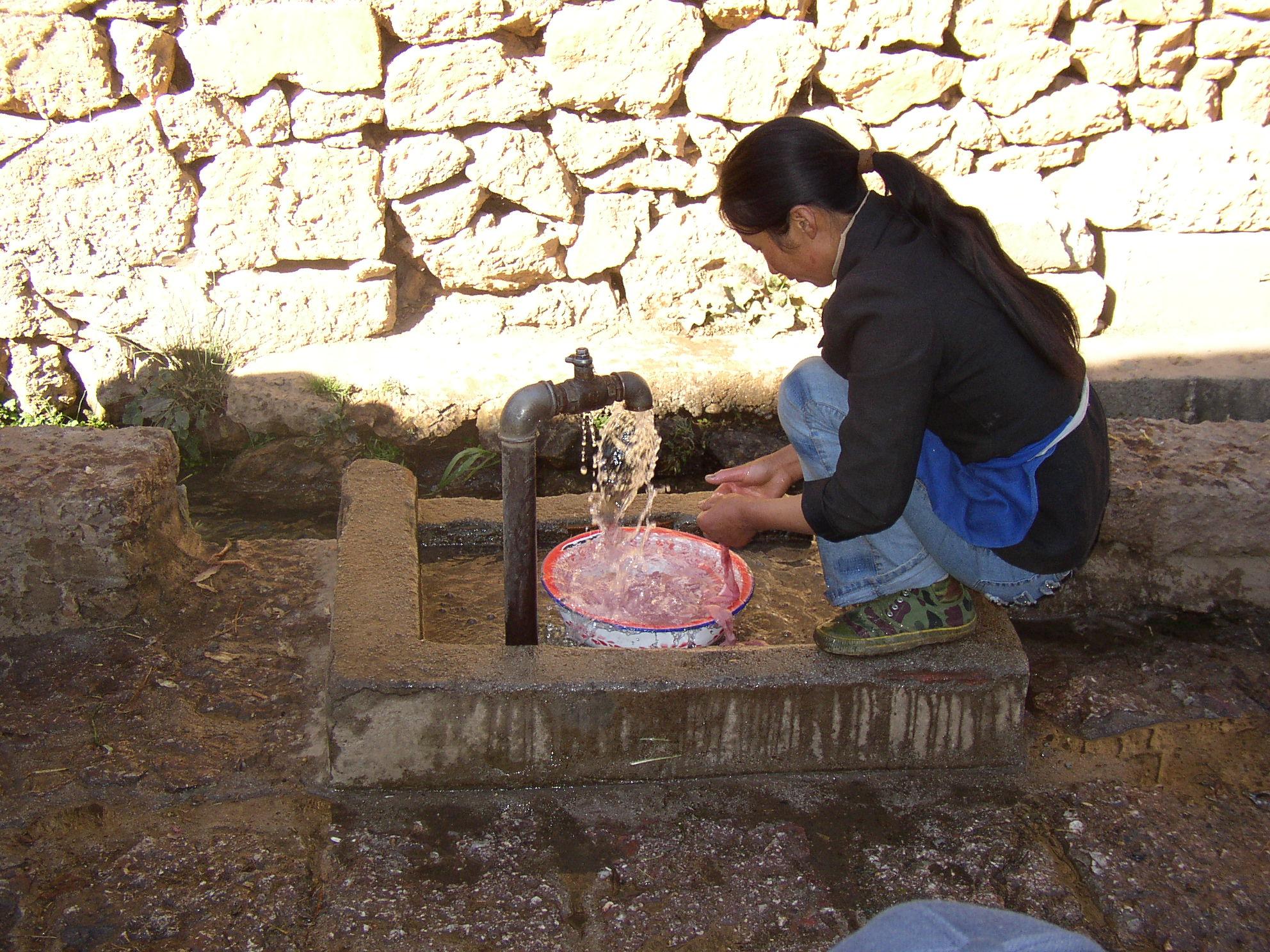 ナシ族の村 腸詰めを洗う女
