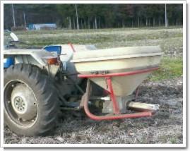 年代物フォード社のトラクターに付けた肥料ふり機械。